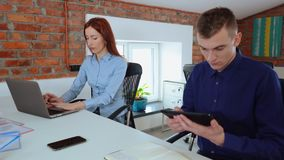 Female and male accountants sitting at the desk, working on a desktop computer and calculating. Coworkers within modern stylish office interior. Footage of stock video footage