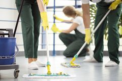 Moping floor and cleaning railing. Coworkers moping the floor and a women dusting a railing in an office Stock Image
