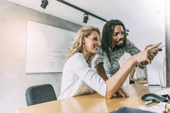 Coworkers in office pointing at desktop Royalty Free Stock Photo
