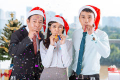 Coworkers with party blowers Royalty Free Stock Image