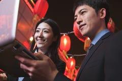 Coworkers pracuje przy nocą na laptopie, miasto ulica, czerwoni lampiony w tle Obrazy Stock