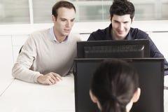 Coworkers siedzi przed działaniem w biurze i komputerem wpólnie zdjęcia stock