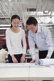 Coworkers smiling analyzing architecture project in the office Royalty Free Stock Photos