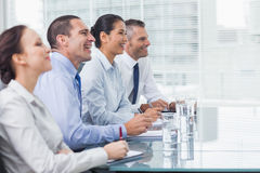 Coworkers smiling while listening to presentation Stock Photos