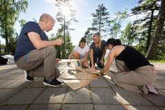 Coworkers Solving Wooden Plank Puzzle On Patio. Male and female coworkers solving wooden plank puzzle on patio in forest stock image