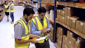 Coworkers som avläser produkter med en barcodebildläsare lager videofilmer