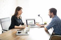 Coworkers som diskuterar en försäljningsrapport arkivbild