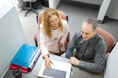 Coworkers som i regeringsställning ser datoren Royaltyfri Fotografi
