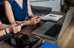 Coworkers som kontrollerar mejl på celltelefoner under arbetsavbrott royaltyfria bilder