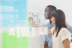 Coworkers standing and looking at sticky notes Stock Image