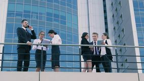 Coworkers standing outdoors and having hot discussion on a busy working day stock footage