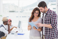 Coworkers standing and using tablet together Royalty Free Stock Images