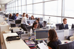 Coworkers at their desks in a busy, open plan office Royalty Free Stock Images