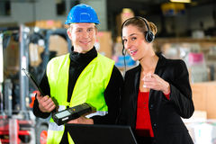 Coworkers at warehouse of forwarding company. Teamwork - female supervisor and warehouseman or forklift driver with laptop and cell phone at warehouse of freight royalty free stock images