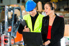 Coworkers at warehouse of forwarding company. Teamwork - warehouseman or forklift driver and female supervisor with laptop, headset and cell phone, at warehouse stock photos