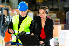 Coworkers at warehouse of forwarding company. Teamwork - warehouseman or forklift driver and female supervisor with laptop, headset and cell phone, at warehouse royalty free stock photos