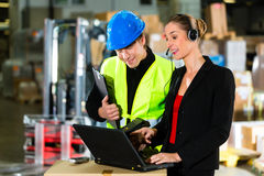 Coworkers at warehouse of forwarding company. Teamwork - warehouseman or forklift driver and female supervisor with laptop, headset and cell phone, at warehouse stock photo