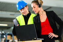 Coworkers at warehouse of forwarding company. Teamwork - warehouseman or forklift driver and female supervisor with laptop, headset and cell phone, at warehouse royalty free stock image