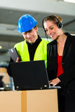 Coworkers at warehouse of forwarding company. Teamwork - warehouseman or forklift driver and female supervisor with laptop, headset and cell phone, at warehouse royalty free stock images