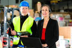 Coworkers at warehouse of forwarding company. Teamwork - warehouseman or forklift driver and female supervisor with laptop, headset and cell phone, at warehouse stock images