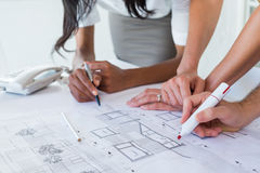 Coworkers working on blueprints together Stock Photography