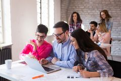 Coworkers working on project together in office. Business Coworkers and architects working on project together in office Royalty Free Stock Images