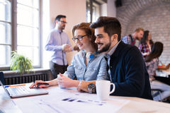 Coworkers working on project together in office Stock Images