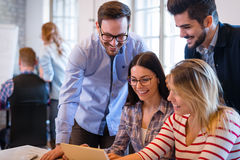 Coworkers working on project together in office Stock Photography