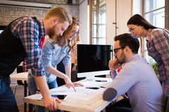 Coworkers working on project together in office Royalty Free Stock Image