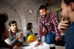 Coworkers working together as team and discussing ideas royalty free stock photo