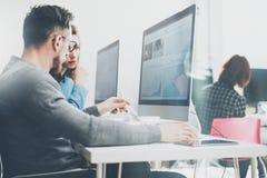 Coworking过程 照片年轻企业乘员组与新的起始的项目现代办公室一起使用 在木头的台式计算机 免版税库存照片