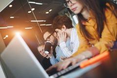 Coworking队激发灵感在现代办公室 工作环境在会议室 年轻创造性的经理合作与新的s一起使用 免版税库存图片