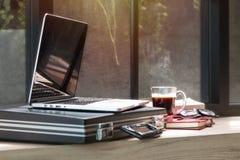 打开膝上型计算机、文件袋子、玻璃和书在coworking的事务 免版税库存图片