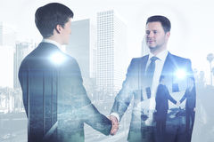 Coworking concept. Side view of happy businessmen shaking hands on bright city background with business chart. Coworking concept. Double exposure Stock Photos