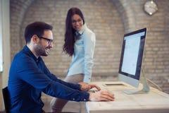 Coworking e colegas incorporados que trabalham no escritório Imagem de Stock
