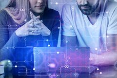 Coworking and innovation concept. Unrecognizable businesspeople using laptop with digital business hologram at modern office workplace. Coworking and innovation Stock Images