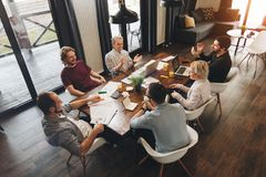 Coworking meeting. Group business people sits around table and w stock photo