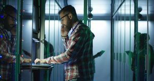 Coworking men in modern server room of data center. Adult man with laptop and tablet working on diagnostics of servers in contemporary data center stock image