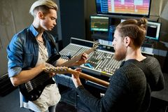 Coworking musicians in recording studio. Two men with guitars playing together while making new song and recording it in sound studio stock image