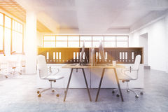 Coworking office with documents toning. Coworking office interior with numerous workplaces, windows with city view and document folders on shelves. Toned image Stock Image