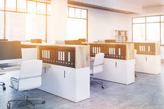 Coworking office side toning. Side view of coworking office interior with computer monitors on several workplaces, cabinets with document folders and windows Royalty Free Stock Image