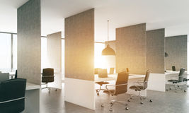 Coworking office with sunlight. Side view of concrete coworking office interior with laptops on workplaces, ceiling lamps and sunlight. 3D Rendering Royalty Free Stock Photo