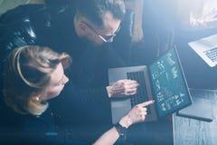 Coworking process i regeringsställning Två unga kollegor som använder datoren Kvinna som bär den svarta sweatern och sitter på so Royaltyfri Foto