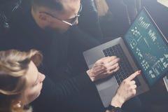 Coworking process i regeringsställning Två unga kollegor som använder datoren Kvinna som bär den svarta sweatern och sitter på so Fotografering för Bildbyråer