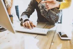 Coworking-Prozess in einem sonnigen Büro Bemannen Sie das Arbeiten an Computer am hölzernen Tisch Weibliche Hand, die zum Tischpl Lizenzfreie Stockfotografie