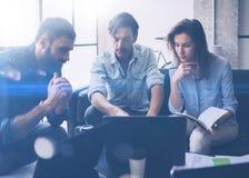 Coworking-Prozess in einem sonnigen Büro Junge Leute, die an Computer arbeiten und tragbare Geräte verwenden Geschäftsteam, das a Lizenzfreies Stockfoto