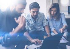 Coworking-Prozess in einem sonnigen Büro Junge Leute, welche die Diskussion im Büro machen Geschäftsteam, das auf dem Sofa und de Stockfoto