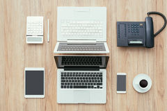 Coworking space. Business desktop and coworking space with two laptops, tablet, calculator and telephone, top view royalty free stock photo