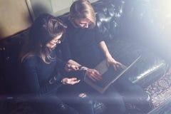 Coworkingsproces in een zonnig bureau Twee jonge meisjes die aan computer werken en mobiele apparaten met behulp van Vrouw die zw Royalty-vrije Stock Foto's