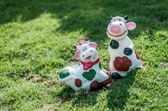 Cows figurines on the grass. A shot of two cows clay figurines on the grass Royalty Free Stock Image